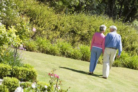 affectionate action: Senior pareja caminando a trav�s de un jard�n de flores