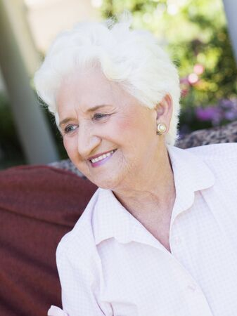 offset angle: Senior woman sitting outdoors on a chair Stock Photo