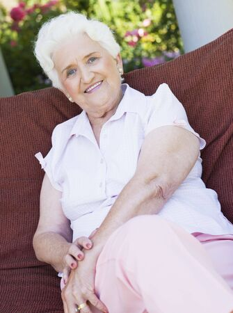 offset up: Senior woman sitting outdoors on a chair Stock Photo