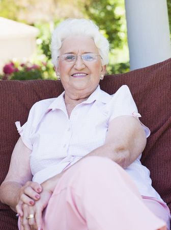 house series: Senior woman sitting outdoors on a chair Stock Photo
