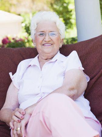 one senior adult woman: Superior al aire libre mujer sentada en una silla  Foto de archivo