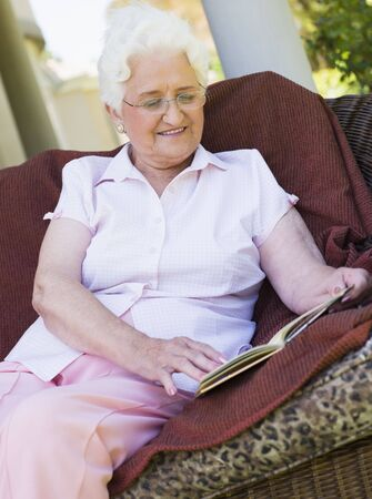 offset views: Senior woman sitting outdoors on a chair reading a book