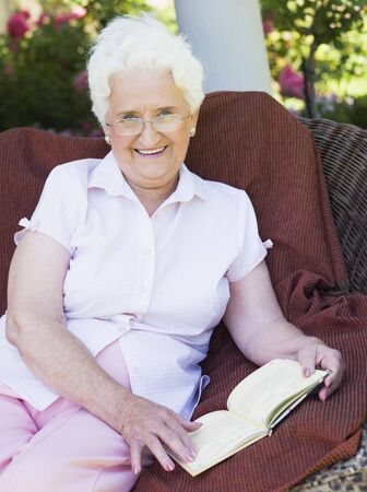 Senior woman sitting outdoors on a chair reading a book photo
