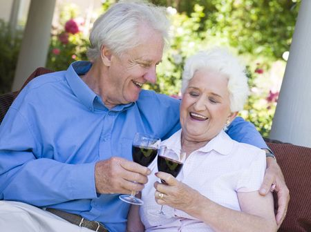 offset views: Senior couple sitting outdoors having a glass of red wine
