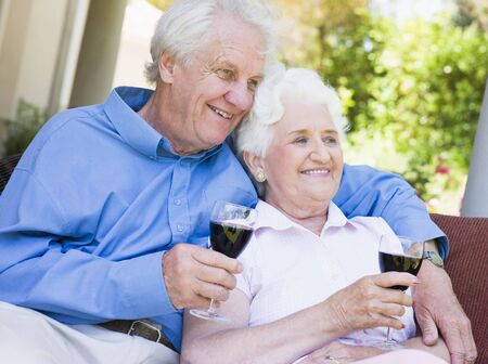 Senior couple sitting outdoors having a glass of red wine photo