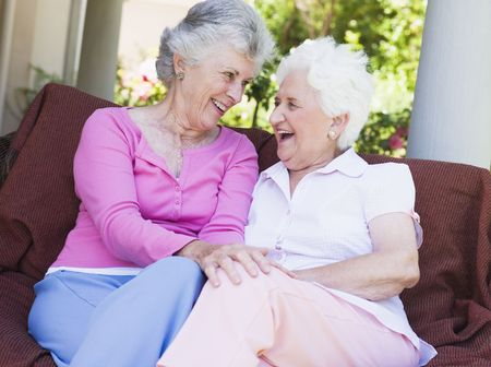 female senior adults: Two senior women sitting outdoors on a chair Stock Photo