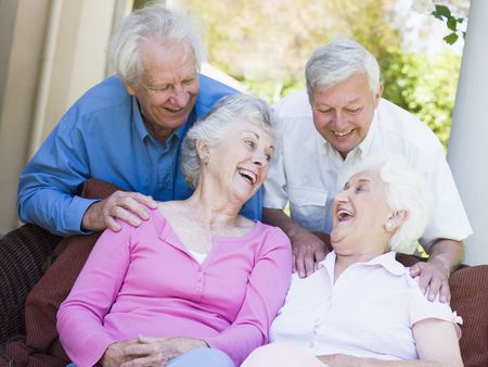 elderly couples: Two senior women sitting outdoors on a chair Stock Photo