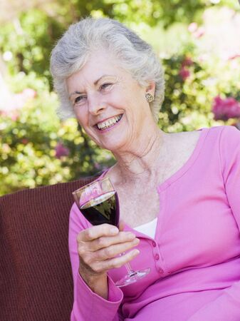 Senior woman sitting outdoors on a chair with a glass of red wine photo