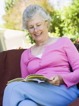 golden years series: Senior woman sitting outdoors on a chair reading a book