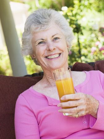 Senior woman sitting outdoors with a glass of orange juice photo