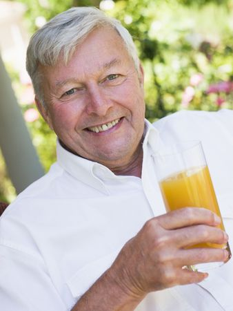 golden years series: Senior man sitting outdoors with a glass of orange juice Stock Photo