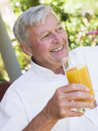 Senior man sitting outdoors with a glass of orange juice Stock Photo - 3177561