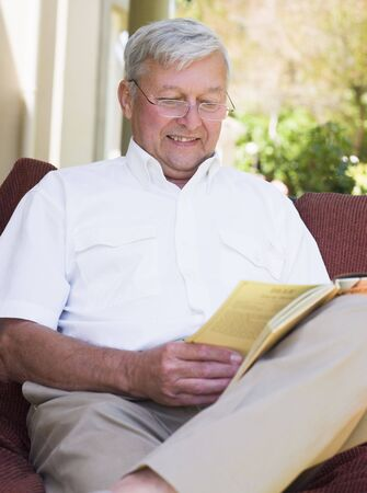 Senior  sitting outdoors on a chair reading a book Stock Photo - 3177528
