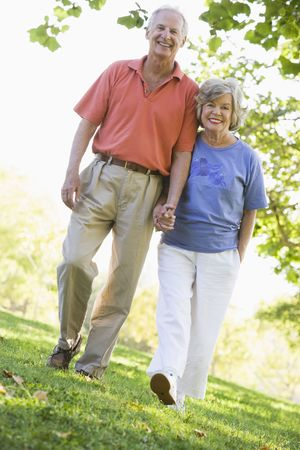 Senior couple walking in park together photo