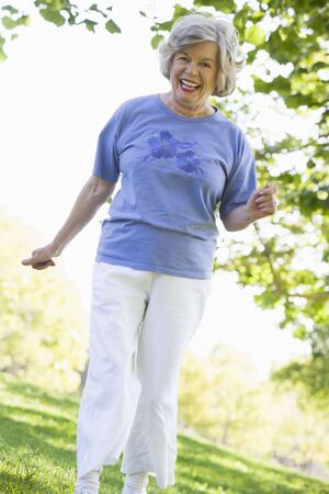 looking towards camera: Senior woman walking in park Stock Photo
