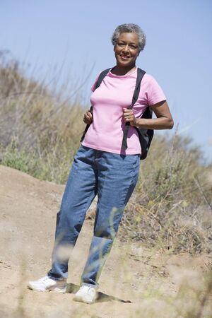 one senior adult woman: Senior mujer caminando sobre un sendero