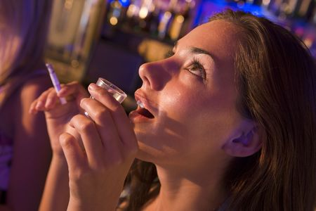 colored gels: Young woman in a bar smoking Stock Photo