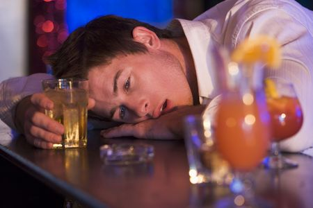 Drunk young man passed out in bar Stock Photo