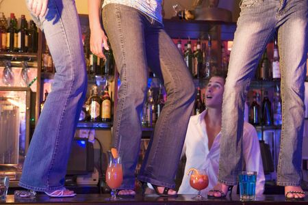 gels: Young people dancing on a bar counter with bartender looking on Stock Photo