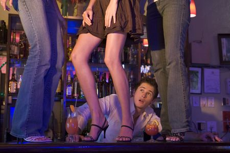 night club series: Young people dancing on a bar counter with bartender looking on Stock Photo