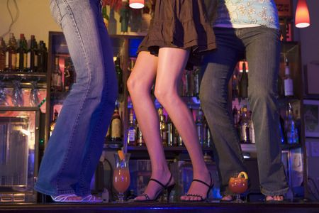 Young people dancing on a bar counter photo