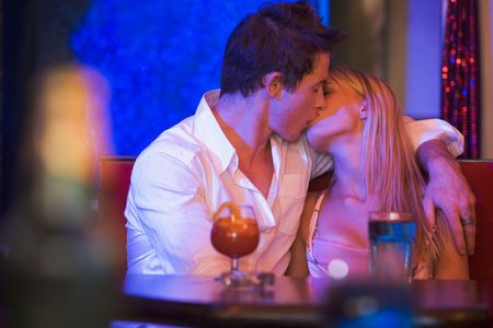 colored gels: Young couple kissing in a bar