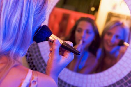 Two young women applying makeup in a mirror photo