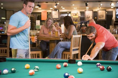 billiards cues: Two men playing pool Stock Photo