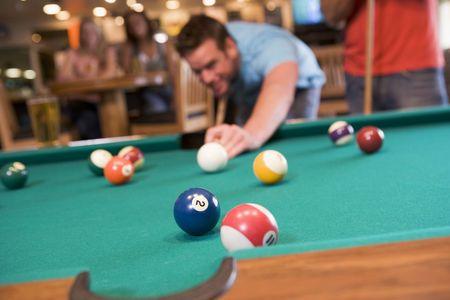 cue sticks: Man playing pool Stock Photo