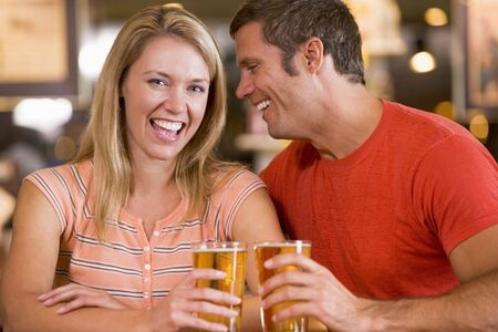 looking towards camera: Couple having beer together