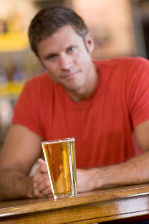 looking towards camera: Man having a glass of beer