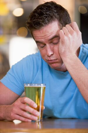 Innebriated man with glass of beer photo