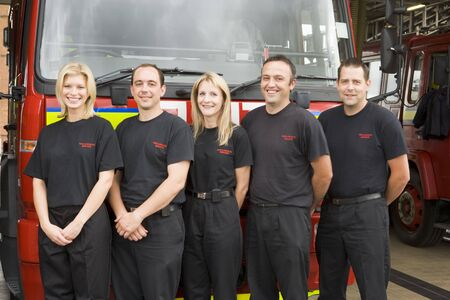 Five firefighters standing in front of fire engine photo