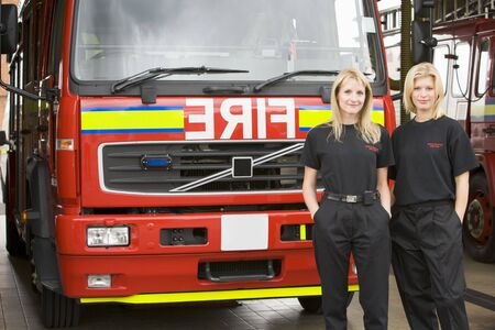 Two firefighters standing in front of fire engine photo