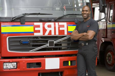 Fireman standing in front of fire engine photo