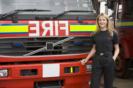 Firewoman standing in front of fire engine photo