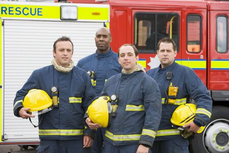 frontal views: Four firefighters standing by fire engine Stock Photo