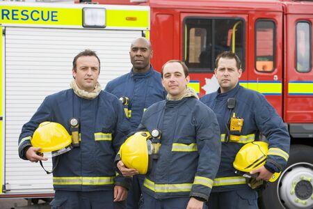 voiture de pompiers: Quatre pompiers debout par un incendie moteur