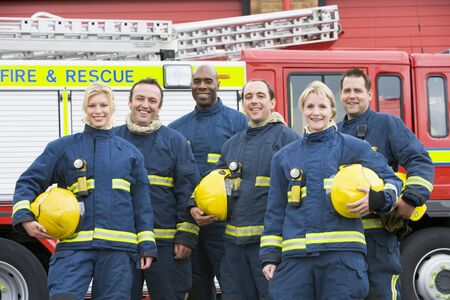 Six firefighters standing by fire engine photo