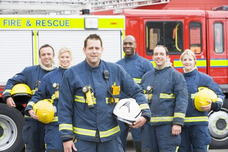 facing on the camera: Six firefighters standing by fire engine Stock Photo