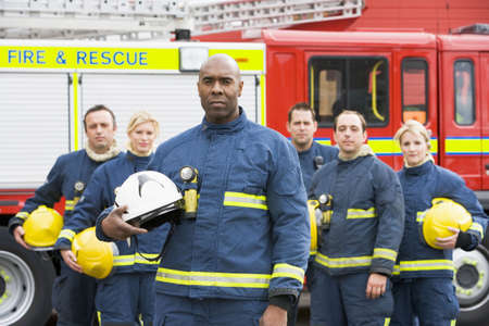 frontal views: Six firefighters standing by fire engine Stock Photo