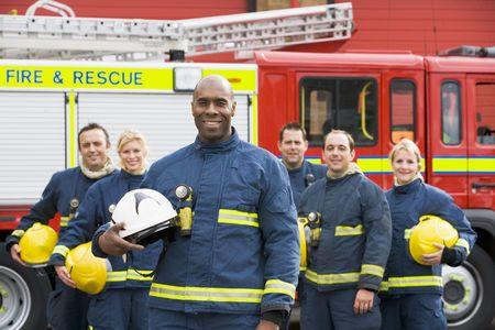 voiture de pompiers: Six pompiers debout par un incendie moteur