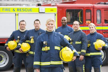 medium group: Six firefighters standing by fire engine Stock Photo