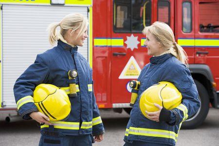 motor ardiendo: Dos firewomen permanente de bomberos de hablar