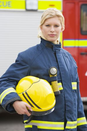 Firewoman standing by fire engine photo