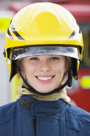 Firewoman standing by fire engine wearing helmet Stock Photo - 3204870