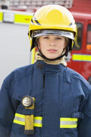 Firewoman standing by fire engine wearing helmet photo