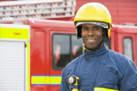 Fireman standing by fire engine wearing helmet Stock Photo - 3200418