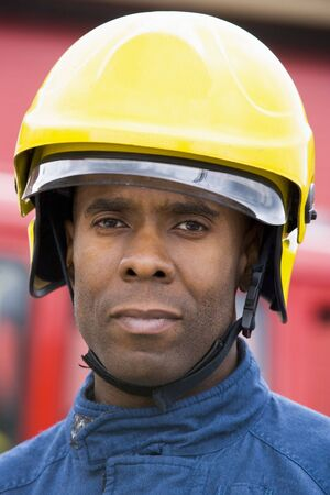 Fireman standing by fire engine wearing helmet Stock Photo - 3201197