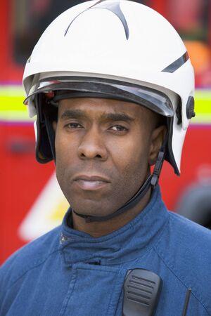 voiture de pompiers: Fireman debout par le port du casque de pompier Banque d'images